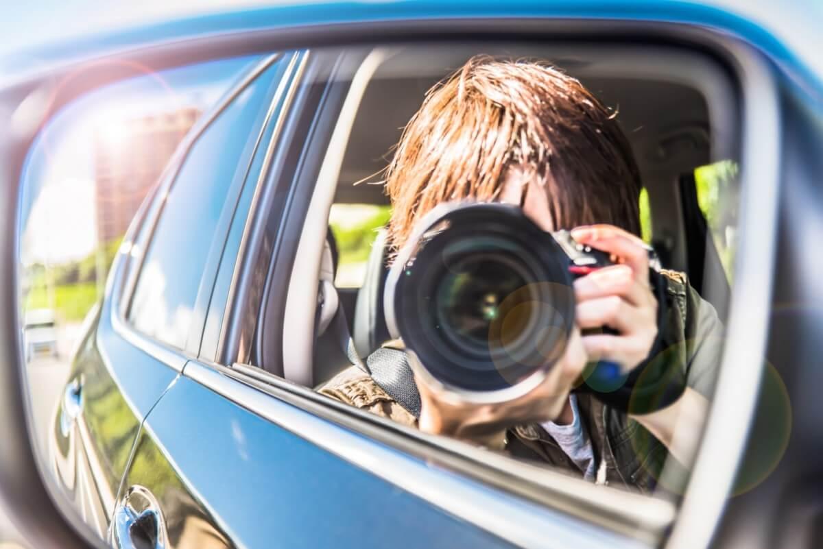 車の中からカメラで浮気の証拠をとっている探偵