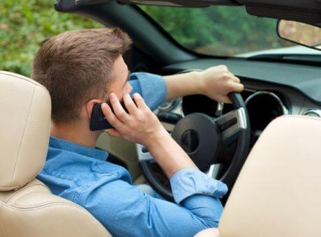 車の中で浮気相手の女性と電話をする男性