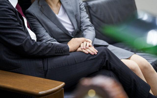 職場で男性の手を握っている妻