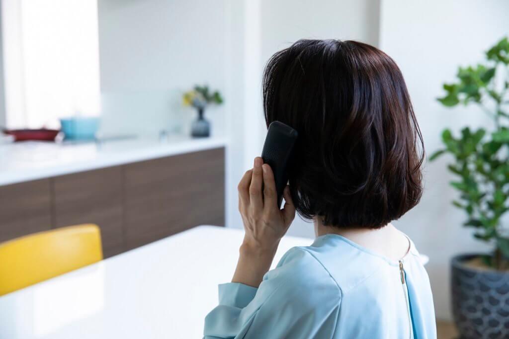 浮気調査依頼で電話をしている女性