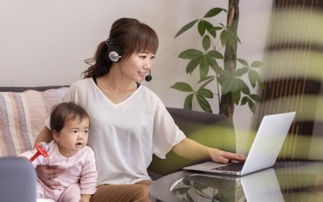 赤ちゃんを抱きながら自宅で仕事している女性